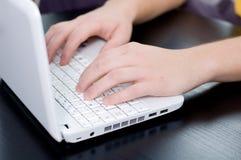 Männliche Hände auf einer Notizbuchtastatur Lizenzfreies Stockfoto