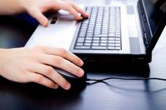 Männliche Hände auf Notizbuchtastatur und -maus Stockbilder
