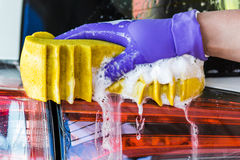 Männliche Hände in den Handschuhen, Waschanlage mit gelbem Schwamm Stockfotografie
