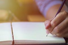 Männliche Hände des Geschäfts mit Bleistiftschreiben auf Papiernotizbuch Stockfotografie