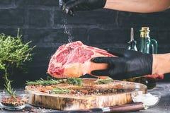 Männliche Hände des Metzger- oder Kochholdingkriegsbeil-Rindfleischsteaks auf dunklem rustikalem Küchentischhintergrund lizenzfreie stockfotos