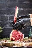 Männliche Hände des Metzger- oder Kochholdingkriegsbeil-Rindfleischsteaks auf dunklem rustikalem Küchentischhintergrund stockbilder