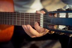 Männliche Hände, die auf der Akustikgitarre im Freien spielen Selektiver Fokus Stockbild
