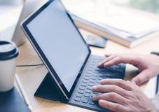 Männliche Hände, die auf elektronischer Tablettentastaturdockstation schreiben Blogger, der am Studio beim Sitzen am Holztisch ar Stockfotos