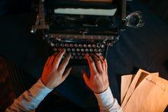 Männliche Hände, die auf Retro- Schreibmaschine schreiben Stockfoto