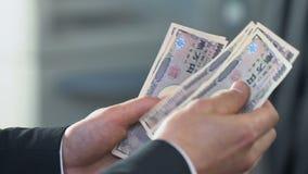 Männliche Hände, die das Geld, japanische Yen an der Bankfiliale austauschend, Finanzierung zählen stock video