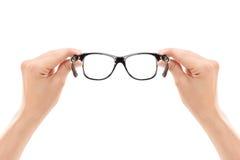 Männliche Hände, die ein Paar Gläser halten Stockbild