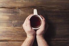 Männliche Hände, die eine weiße Schale mit Tee auf einem Hintergrund von altem hölzernem halten Lizenzfreies Stockbild