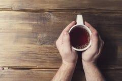 Männliche Hände, die eine weiße Schale mit Tee auf einem Hintergrund von altem hölzernem halten Stockbild