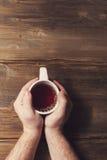 Männliche Hände, die eine weiße Schale mit Tee auf einem Hintergrund von altem hölzernem halten Lizenzfreie Stockfotografie
