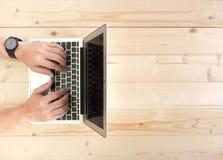 Männliche Hände, die an einem Laptop auf einem hölzernen Desktop arbeiten Stockbild