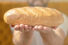 Männliche Hände, die frisch gebackenes wheaten Brot halten lizenzfreie stockfotografie