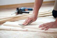Männliche Hände, die hölzerne Planke polieren Stockfotos