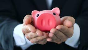 Männliche Hände, die heraus Sparschwein, Geldeinsparungskonzept, Firmenbudget, Finanzierung halten stock footage