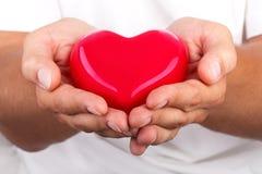 Männliche Hände, die rotes Herz geben Stockfotografie