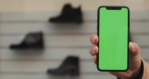 Männliche Hände, die schwarzen Smartphone mit grünem Schirm auf dem Speicher mit Schuhhintergrund halten Großer Bildschirm Zwei i stock video