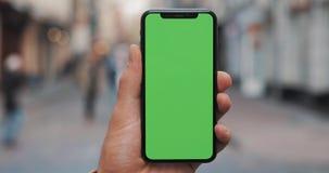 Männliche Hände, die schwarzes intelligentes Telefon mit grünem Schirm auf Stadtstraßenhintergrund halten Großer Bildschirm Zwei  stock video