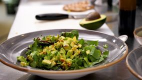 Männliche Hände, die souce gießen und Avocadosalat würzen stock video