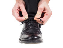 Männliche Hände, die Spitzee auf schwarzen Lederschuhen binden stockfoto