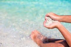 Männliche Hände in Form von Herzen mit Kieseln nach innen auf weißem Strand Lizenzfreie Stockfotografie