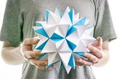 Männliche Hände halten polygonalen Papierstern, geometrische Zahl des futuristischen blauen Origamis Stockbild