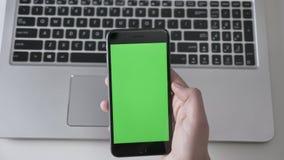 Männliche Hände klopfen auf einem größeren schwarzen Smartphone, laptpo im Hintergrund Grüner Schirm, chromakey Konzept, Laptop i stock video footage
