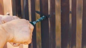 Männliche Hände reparieren den Zaun mit Spezial-Schrauben und Handbuchschraubenzieher stock video