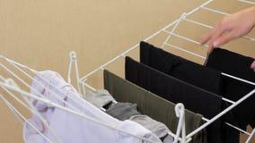 Männliche Hände, welche heraus die Kleidung im Trockner hängen Trocknen der gewaschenen Kleidung Ein Mann tut Hausarbeiten stock footage