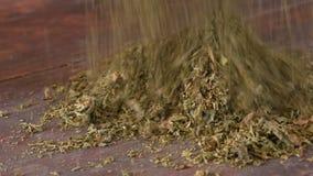 Männliche Hände zerknittern trockene Blätter des Tabaks auf Tabelle stock video