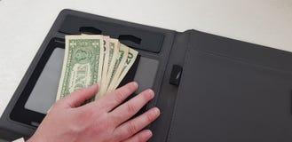 Männliche Hand auf Bündel Dollarscheinen lizenzfreies stockfoto