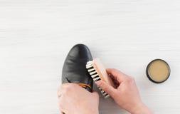 Männliche Hand bürstete mit Sahne schwarze Schuhe auf Weiß Stockfotografie