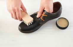 Männliche Hand bürstete mit Sahne schwarze Schuhe auf Weiß Lizenzfreie Stockfotos