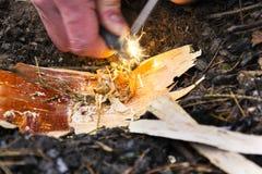 Männliche Hand beginnt Feuer mit Magnesiumfeuerstahl, Feuerschlaggerät Stockbild