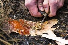 Männliche Hand beginnt Feuer mit Magnesiumfeuerstahl, Feuerschlaggerät Stockfotos