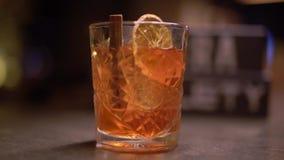 Männliche Hand bewegt den Alkohol, der mit Einteiler der Orange geschossen wird und Zimt schließen auf dem Tisch oben stock footage