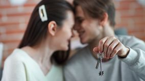 Männliche Hand der Nahaufnahme, die Schlüssel von glaubender Liebe der neuen Wohnungsfamilien-Paare im Hintergrund hält stock video footage