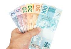 Männliche Hand, die alle Brasilianer Reaisanmerkungen hält Lizenzfreies Stockfoto