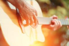 Männliche Hand, die auf Akustikgitarre spielt Stockbilder