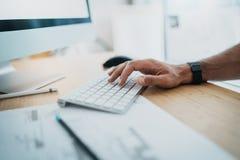 Männliche Hand, die auf Computertastatur schreibt Blogger, der am Studio beim Sitzen am Holztisch arbeitet horizontal verwischt Lizenzfreie Stockfotos