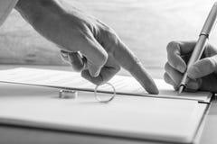 Männliche Hand, die auf eine Frau zeigt, wo man legale Scheidungspapiere unterzeichnet Stockbilder