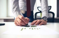 Männliche Hand, die auf Geschäftsdokument während der Diskussion bei der Sitzung zeigt Stockfotografie
