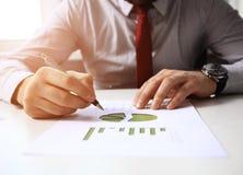Männliche Hand, die auf Geschäftsdokument während der Diskussion bei der Sitzung zeigt Stockbild
