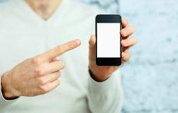 Männliche Hand, die auf Smartphoneanzeige zeigt Stockfotos
