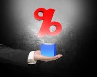 Männliche Hand, die blauen Block mit rotem Prozentsatzzeichen hält Stockbild