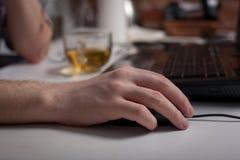 Männliche Hand, die Computermaus mit Laptoptastatur im Hintergrund hält Stockfotos
