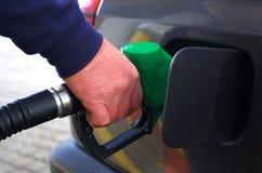 Männliche Hand, die das Auto mit Brennstoffpistole auf einer Tankstelle wieder füllt Lizenzfreies Stockfoto