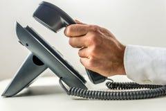 Männliche Hand, die den Empfänger eines Telefons aufhebt lizenzfreies stockbild
