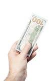 Männliche Hand, die 100 Dollar lokalisiert auf Weiß hält Lizenzfreie Stockfotografie