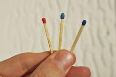 Männliche Hand, die drei Sicherheitsmatch, jedes mit einer anderen Farbe seiner Spitze als Symbol der schwierigen Wahl und Wahl h Stockfotos