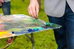 Männliche Hand, die dunkelgrüne Farben mit einem paletteknife mischt Stockfotografie